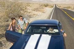 Young couple hitchhiking on desert road, in conversation with driver of car,  Stock Photos
