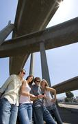 Small group of friends by car looking at mobile phone beneath overpass, low a Stock Photos