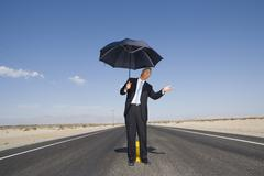 businessman on open road in desert with umbrella, feeling for rain, low angle - stock photo