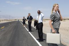 Small group of businessmen and women using mobile phones on side of road in d Stock Photos