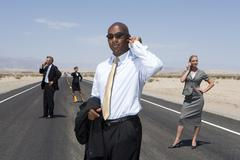 Small group of businessmen and women using mobile phones on road in desert, l Stock Photos