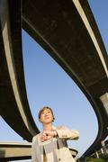 Businesswoman looking at watch beneath overpasses, low angle view Kuvituskuvat