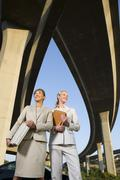 Two businesswomen with briefcase and folder beneath overpasses, low angle vie Stock Photos