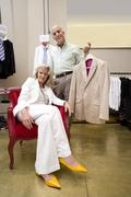 Mature man and woman in shop, woman in armchair, man with suit jacket, portra Stock Photos