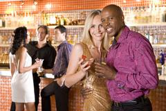 Young couple arm in arm in bar with drinks, smiling, portrait Stock Photos