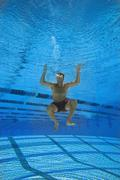 man in swimming pool, underwater view - stock photo