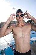 Young man adjusting goggles next to swimming pool Stock Photos