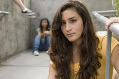 teenage girl (13-15) with hand on railing, friends in background, portrait - stock photo
