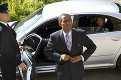 Businessman doing up button of suit jacket, chauffeur holding door of car ope Stock Photos