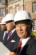 small group of businessmen in hardhats, one with blueprint, portrait - stock photo
