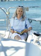 mature woman on boat with book, smiling, portrait - stock photo