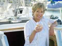 Woman in entrance to cabin of boat with drink, smiling, portrait Stock Photos