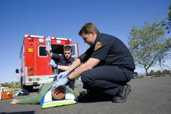 Paramedic and colleague helping man on stretcher, low angle view Stock Photos