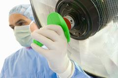 Surgeon adjusting equipment, close-up of hand Stock Photos