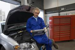 Mechanic with diagnostic computer on car with open bonnet Stock Photos