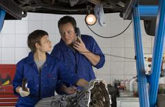 Female mechanic looking at colleague on telephone by engine of elevated car Stock Photos