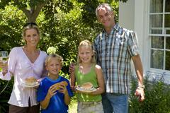 Family of four having barbeque, smiling, portrait Stock Photos