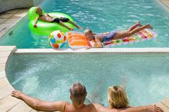 Family of four in swimming pool, boy and girl (7-11) on inflatable chair and  Kuvituskuvat