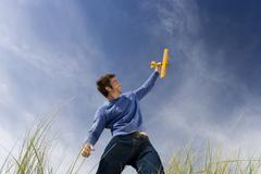 Man holding up toy airplane, standing on long grass, low angle view Stock Photos