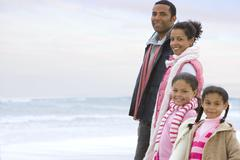 Family of four in row on beach, smiling, portrait Stock Photos