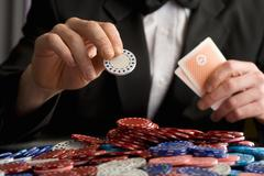 man placing gambling chip on pile of chips on table, mid section - stock photo