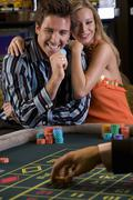 young couple gambling, man with gambling chip, smiling, portrait - stock photo