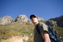 Young man hiking with rucksack, low angle view Stock Photos