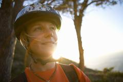 young woman in bicycle helmet, smiling, close-up (lens flare) - stock photo