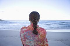 Woman on beach, looking out to sea, rear view Stock Photos