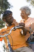 Senior woman adjusting man's bicycle helmet, low angle view Stock Photos