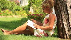 Blonde women reading a book Stock Footage