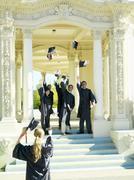 Graduates throwing caps in air in celebration Stock Photos