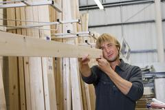 Man checking straightness of timber in diy store Stock Photos