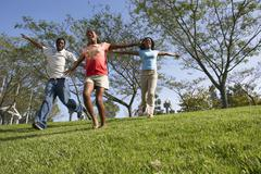 two generation family running down hill in park, arms outstretched, smiling,  - stock photo