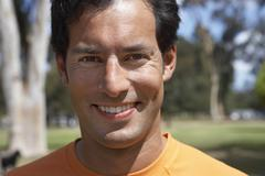 Man standing in park, smiling, front view, close-up, portrait Stock Photos