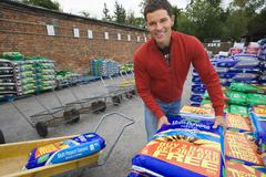 Man loading compost into trolley in garden centre, smiling, portrait Stock Photos