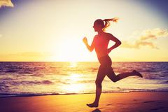 Woman running at sunset Stock Photos
