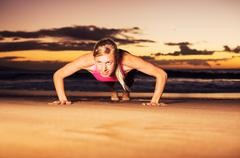 Fitness woman doing push ups Stock Photos