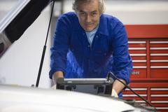 Mechanic with electronic diagnostics machine, portrait Stock Photos