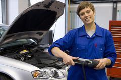 female mechanic with electronic diagnostics device, portrait - stock photo