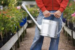 Man carrying watering can in garden centre, front view, mid-section, flowers  Stock Photos