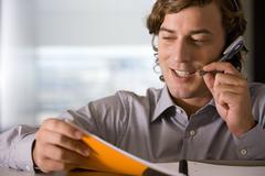 businessman talking on hands-free headset - stock photo