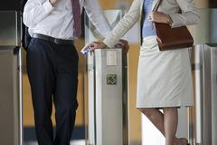 Business people using mass transit turnstile Stock Photos