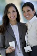 Two businesswoman posing with conference badges Stock Photos