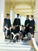 Person video taping young people graduating in caps and gowns Stock Photos