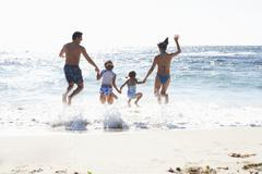 two generation family wearing swimwear, jumping above surf on sandy beach, si - stock photo