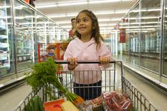 Young girl grocery shopping in frozen foods section Kuvituskuvat