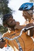 active senior couple preparing to cycle in park, woman adjusting man's cyclin - stock photo