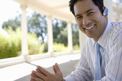 Businessman using hands-free device outdoors Stock Photos