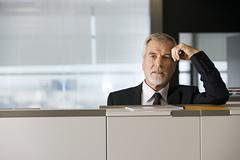 Mature businessman leaning on filing cabinet in office, portrait Kuvituskuvat